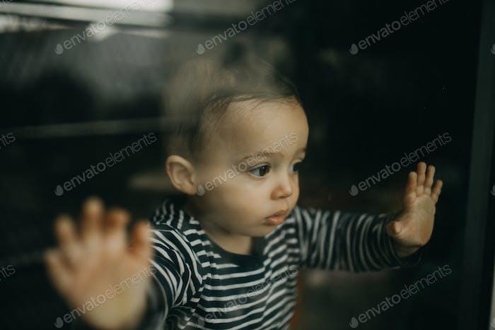 Toddler looking through window
