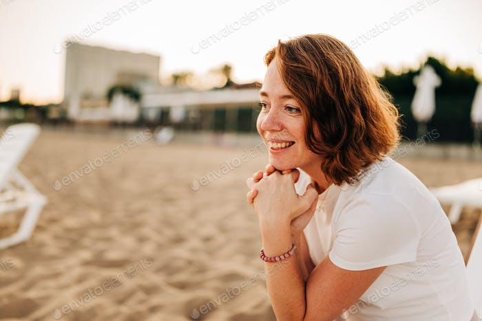 Authentic lifestyle portrait of red hair woman sitting on the sun lounger at the sandy beach