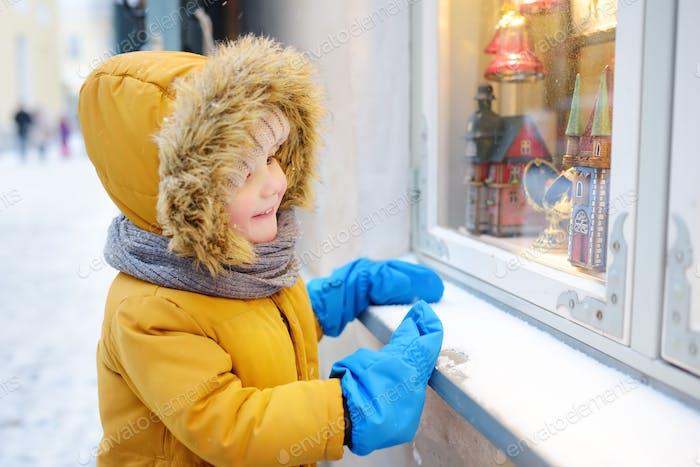 Kleiner Junge Wahl Weihnachtsdekorationen im Schaufenster des Ladens am Wintertag. Tourist auf der Suche nach Weihnachten