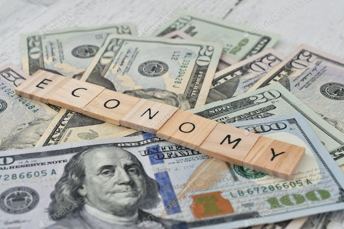 Economy, letter tiles on money - currency cash, prosperity, assets, business, retirement, savings