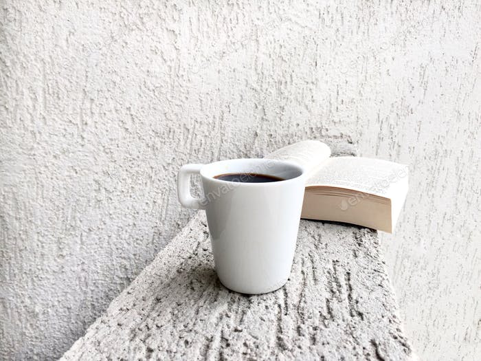 White cup of coffee and book with a white minimalistic background