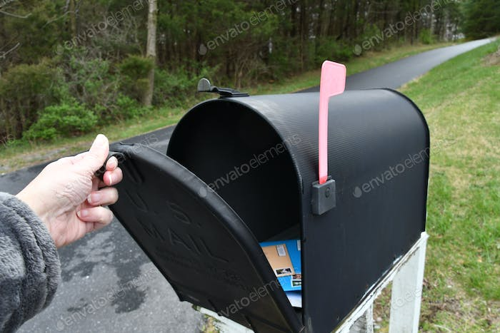 Mailing a small package and envelopes with cards. Putting mail in the mailbox for pickup.