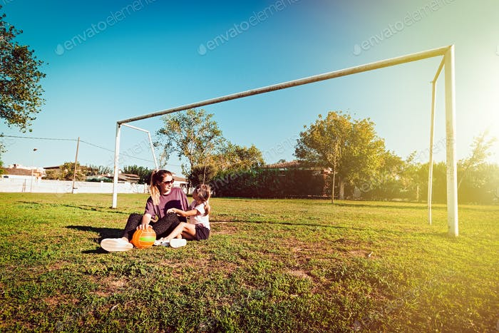 Mom and daughter sitting on grass with ball near football goals, family fun outdoors