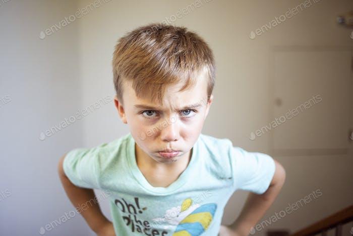 Niño pequeño con una cara enojada