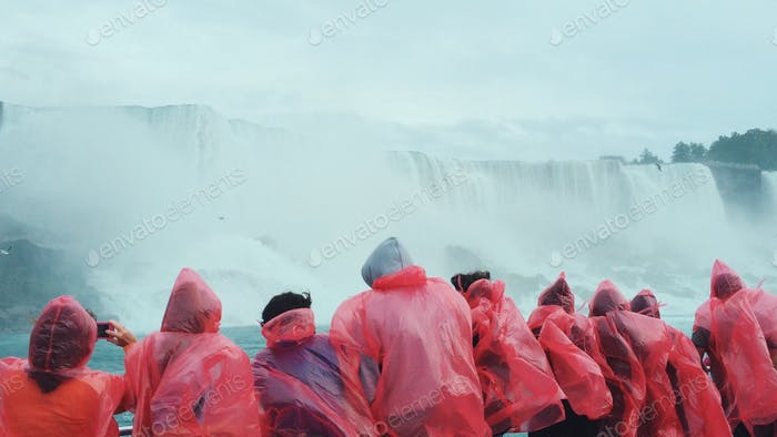 A group of tourists in pink ponchos marvel at Niagara Falls.