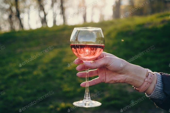 Frau hält Glas rosa Wein