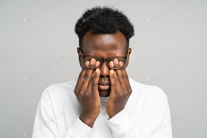 Sleepy young afro-american man in glasses rubbing his eyes, feels tired after working on laptop