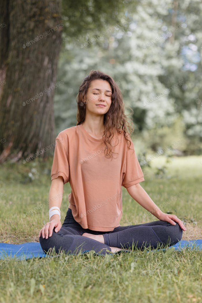 European woman with curly hair in beige t-shirt sitting in lotus pose
