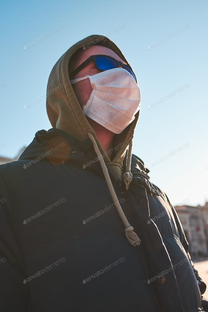 Young man in the hood wearing the face mask to avoid virus infection