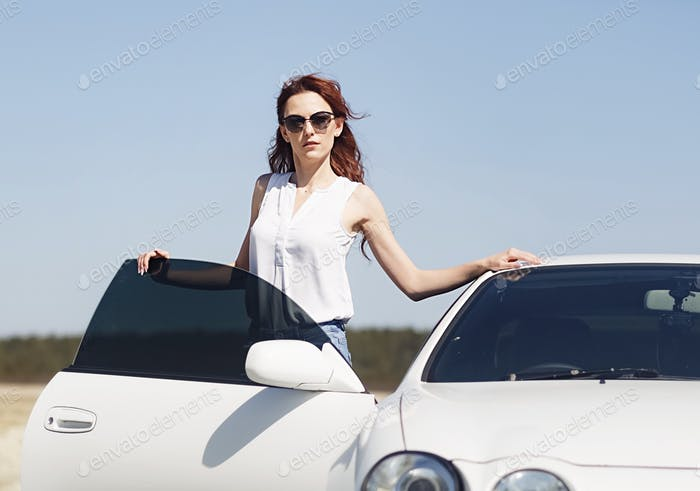 Young attractive woman with white car