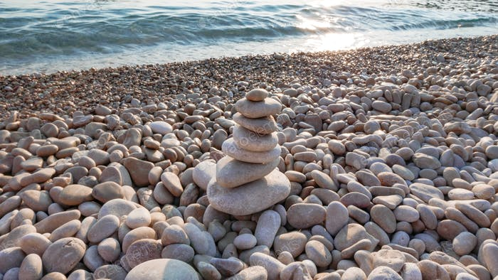 Close-up of stacked stones on beach. Natural light, zen, sea.