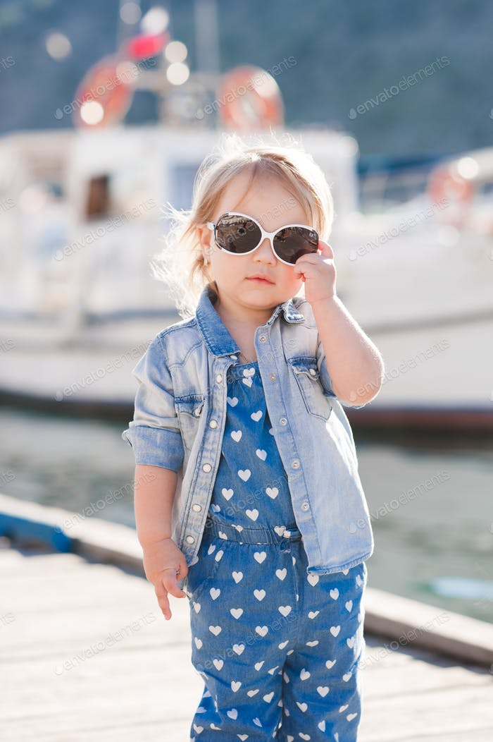 Stylish baby girl 2-3 year old wearing denim clothes outdoors. Looking at camera. Summer time.