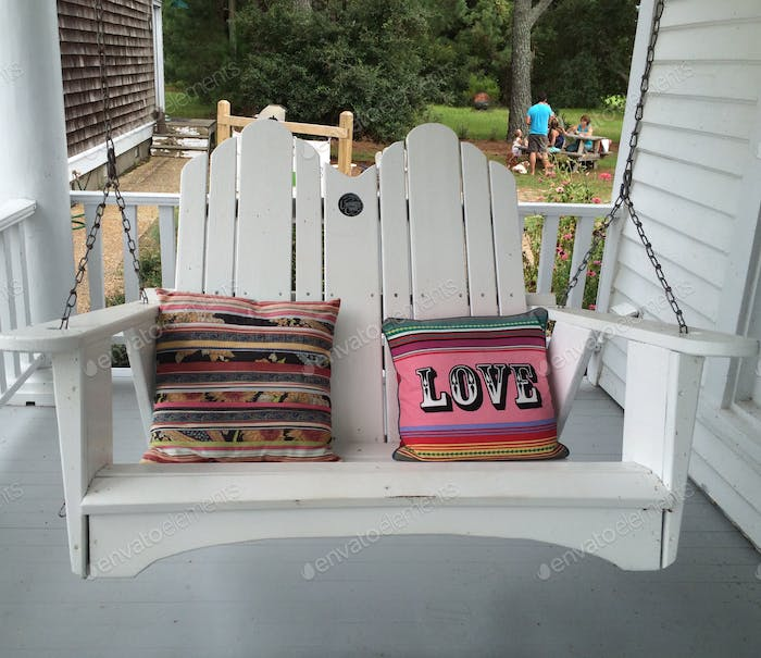 Love to enjoy the outdoors on a swing with colorful pillows & one of them with the word LOVE