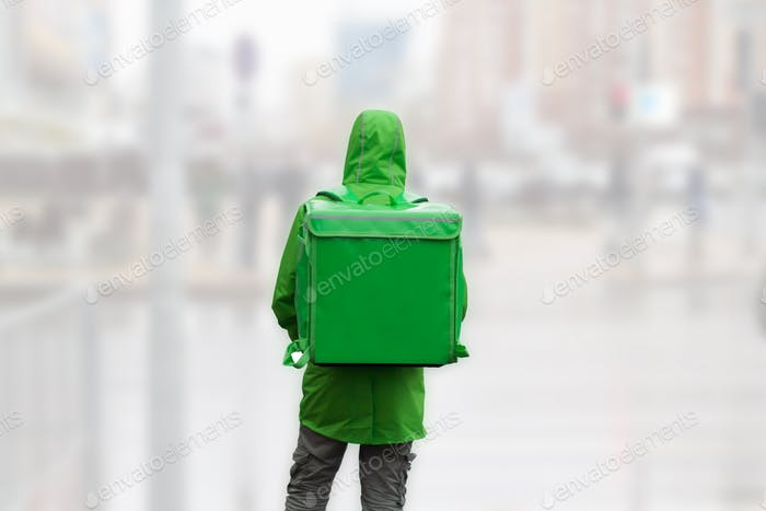 unrecognizable  young man courier in green jacket with green backpack on a background of blurred cit