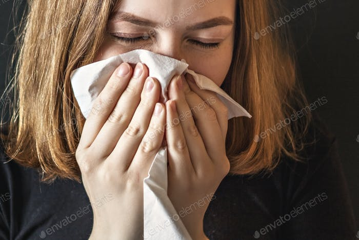 Sick young woman, with wrinkled nose, blowing her nose and sick allergic girl with allergy symptoms