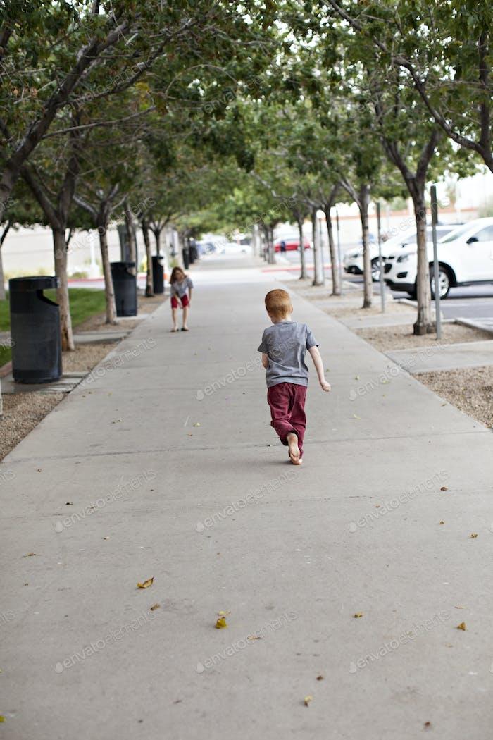 Kinder laufen den Bürgersteig hinunter.