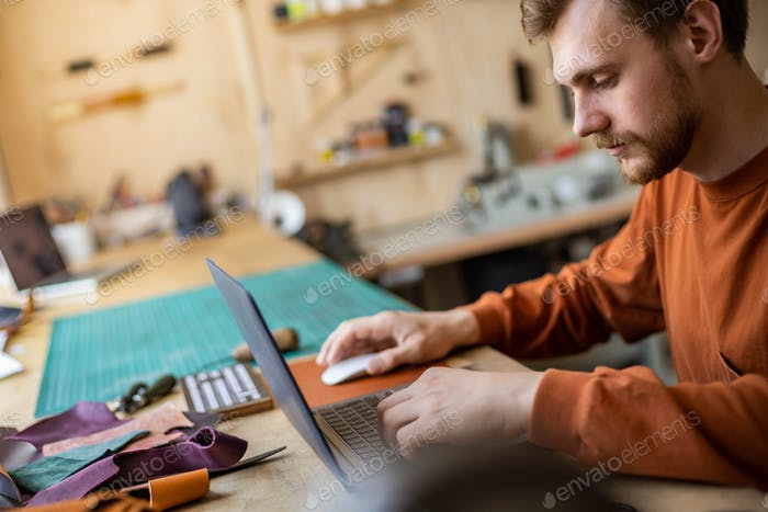 Male tanner working use laptop chatting surfing internet promotion advertisement of leatherwork