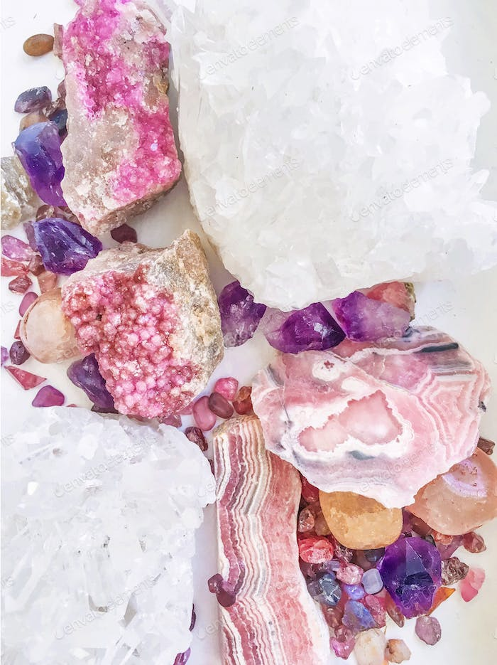Collection of pink and purple gems, minerals, and rocks on a white background.