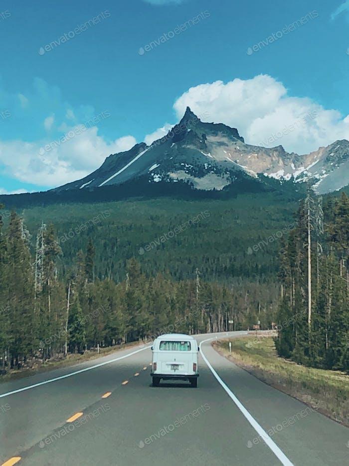 Vista de un pico de montaña desde la autopista mirando el fondo de un autobús VW.
