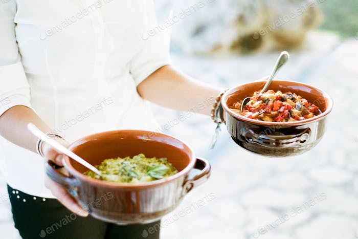 Woman holding two bowls of Italian food
