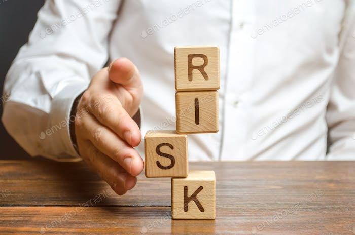 A man straightens a segment in an unstable tower of cubes labeled Risk