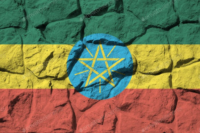 Ethiopia flag depicted in paint colors on old stone wall close up