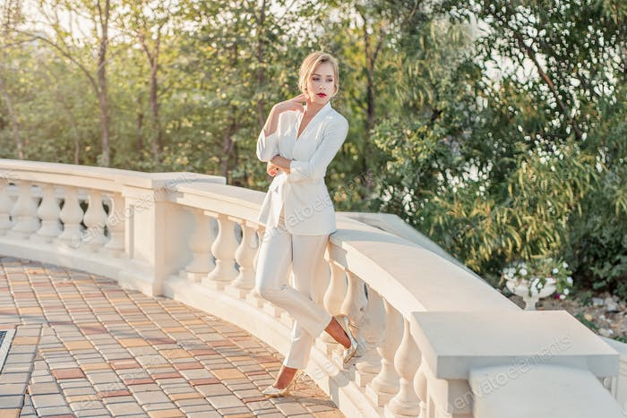 Business young blonde woman in a white pantsuit with red lips stands against the green garden