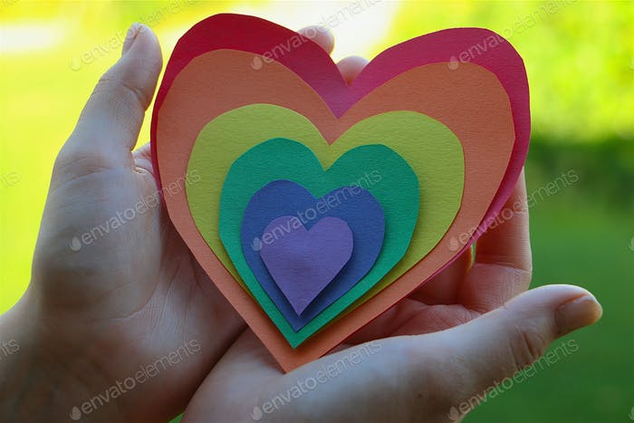 Conceptual image of hands holding rainbow colored hearts