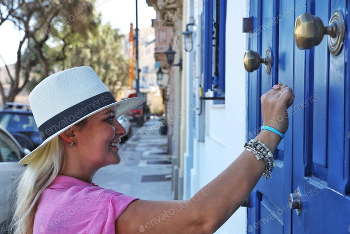 A young woman with the hat knocking on a blue door