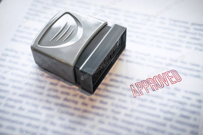 Close up stamp on paper document to approve business investment contract agreement