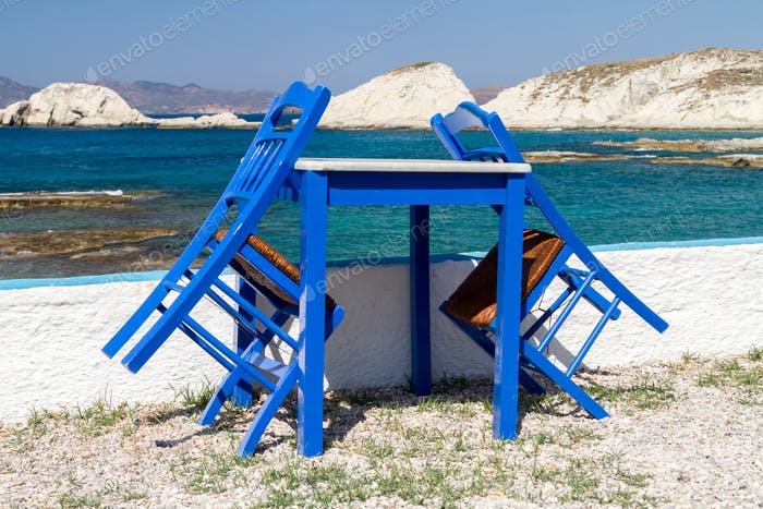 Taverna closed, blue painted chairs and table by the sea with a view of the Cyclades in background.