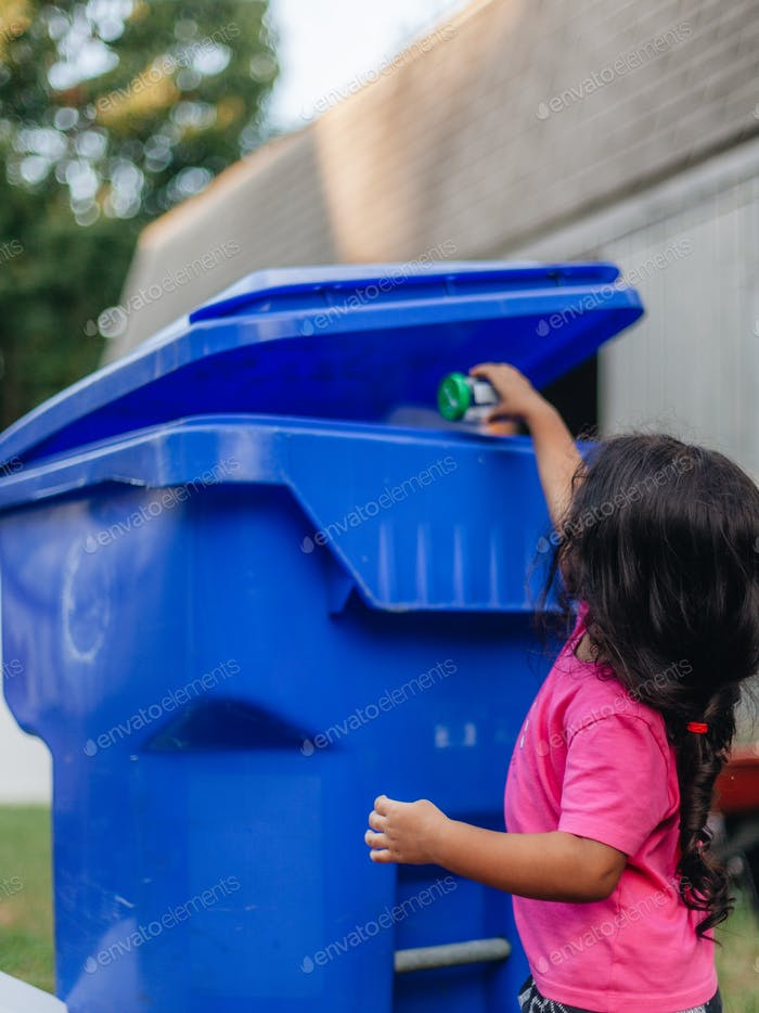 Diverse pre school girl putting glass jar into recycling bin, environmentally friendly, conscious