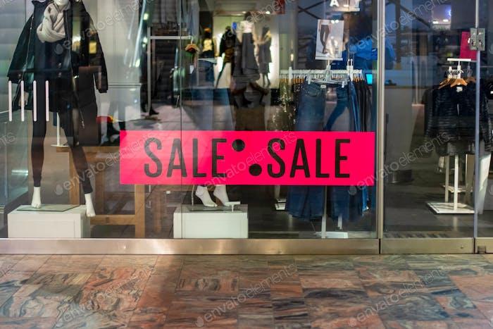 Ein Shop-Front-Display. Verkauf von Werbung in einem Bekleidungsgeschäft. Rosa Plakatzeichen mit dem Wort Sale
