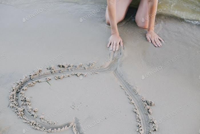 Woman drawing heart on the sand