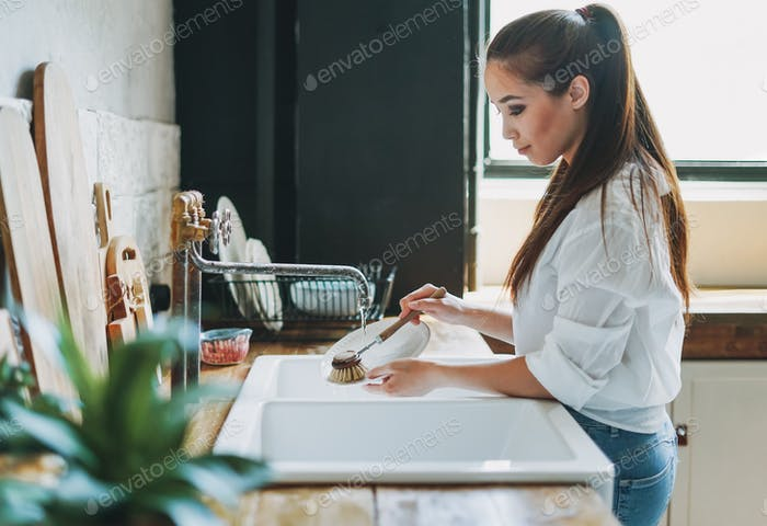Young woman washes dishes with wooden brush with natural bristles at window in the kitchen