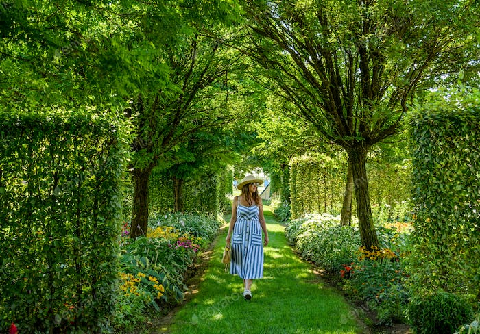 Young woman walking in green park. Greenery, flowers, summer, spring, botany.