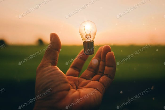 Glowing bulb in hand for bright ideas concept.