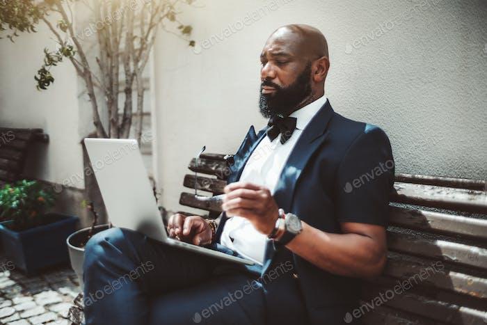 Hombre negro con un portátil en el banco