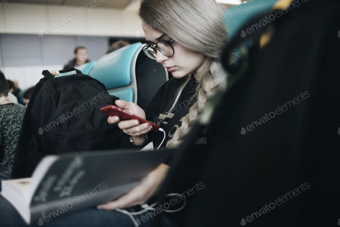 Girl in the airport using mobile