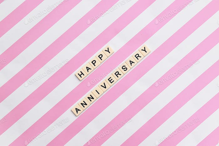 happy anniversary message in letters on pink and white diagonal stripes