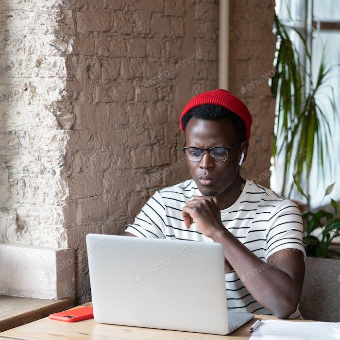Black freelancer man wear wireless headphones watching webinar on laptop remote online work in cafe