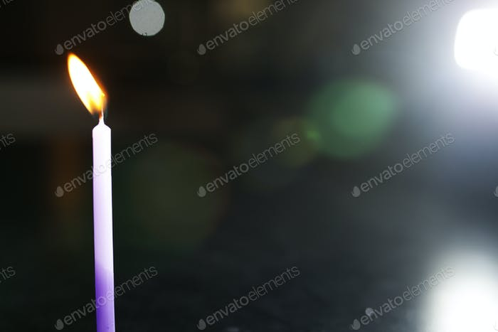 purple lit candles in the dark
