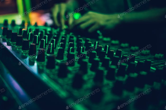 Hands of male dj adjusting sound during disco party.