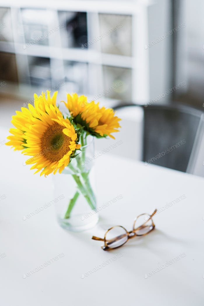 Clean desk with sunflowers and glasses