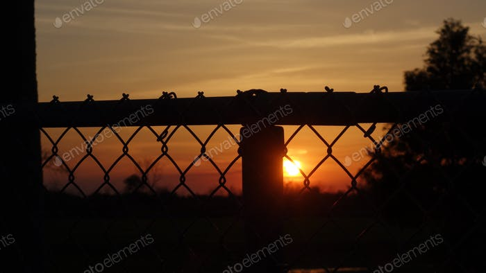 Sun Setting Behind A Chainlink Fence
