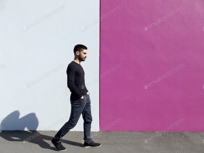 A modern millennial man walking past a pink and white wall