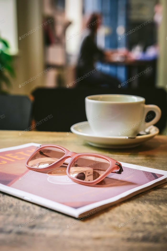 Coffeehouse:Tabletop with coffee cup, magazine, sunglasses and people in background.