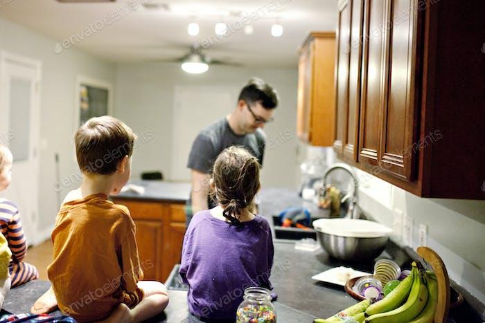kids watch dad unload dishwasher