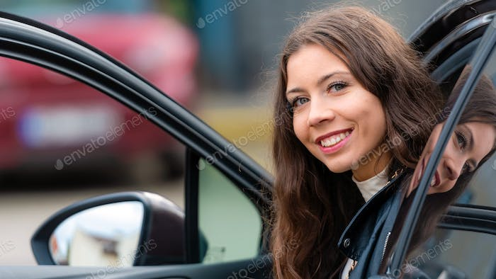 young, smiling woman  sits in a car with an open door and looks back, close-up portrait