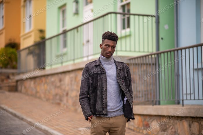 Stylish young man with denim with colorful houses in background